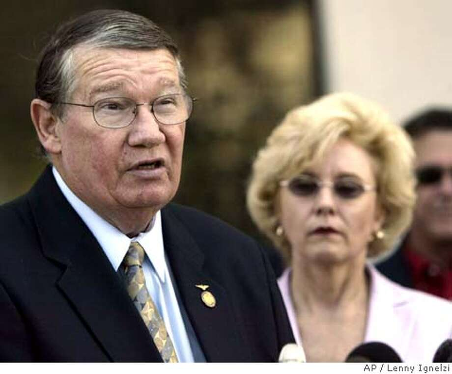 """** RETRANSMISSION FOR IMPROVED TONING ** Rep. Randy """"Duke"""" Cunningham, flanked by his wife Nancy, announces he will not seek re-election, during a news conference Thursday, July 14, 2005, in San Marcos, Calif. The eight-term San Diego-area Republican, under federal investigation for his dealings with a defense contractor, read a brief written statement and did not take questions before ducking back into a library on the California State University, San Marcos campus. (AP Photo/Lenny Ignelzi) RETRANSMISSION FOR IMPROVED TONING Photo: LENNY IGNELZI"""