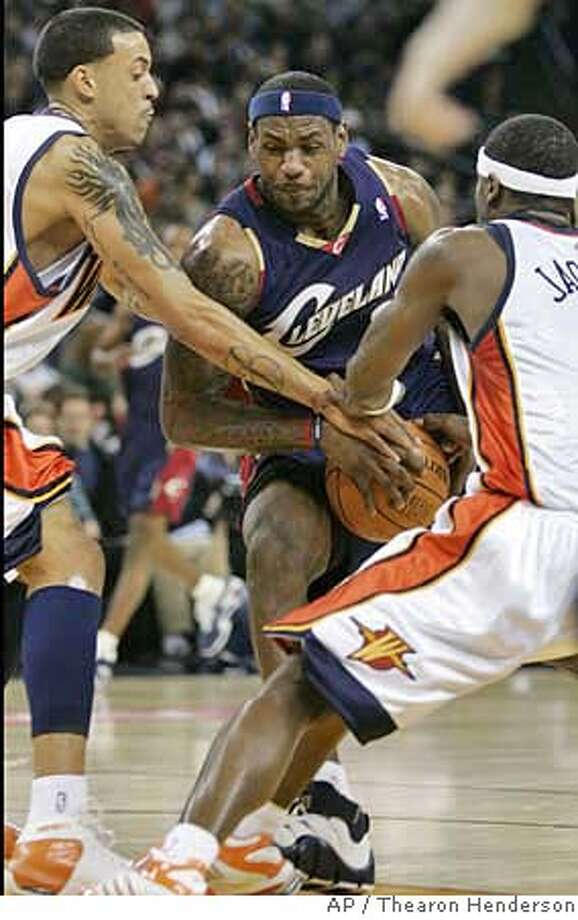Cleveland Cavaliers' LeBron James (23) tries to drive between Golden State Warriors' Matt Barnes, left, and Stephen Jackson, right, during the first quarter of an NBA basketball game in Oakland, Calif., Saturday, Jan. 20, 2007. (AP Photo/Thearon Henderson) Photo: Thearon Henderson