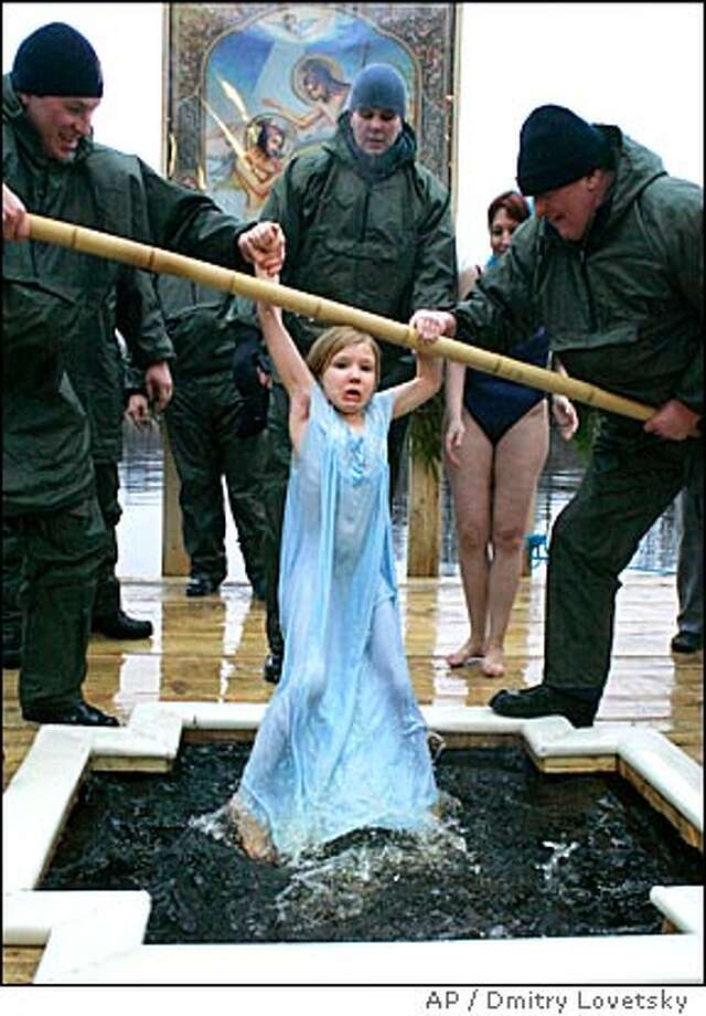 Russian Orthodox believers, help 8-year-old Natalya to get out of icy water after plunging her to celebrate Orthodox Epiphany in the town of Sestroretsk, 30 km (19 miles) west of St. Petersburg, Russia, Friday, Jan. 19, 2007. Believers marked the Orthodox Epiphany by dipping in lakes and rivers across the country, a practice that they believe purifies the soul. This year during an unusually warm winter there is no ice on rivers and ponds. (AP Photo/Dmitry Lovetsky) Photo: DMITRY LOVETSKY