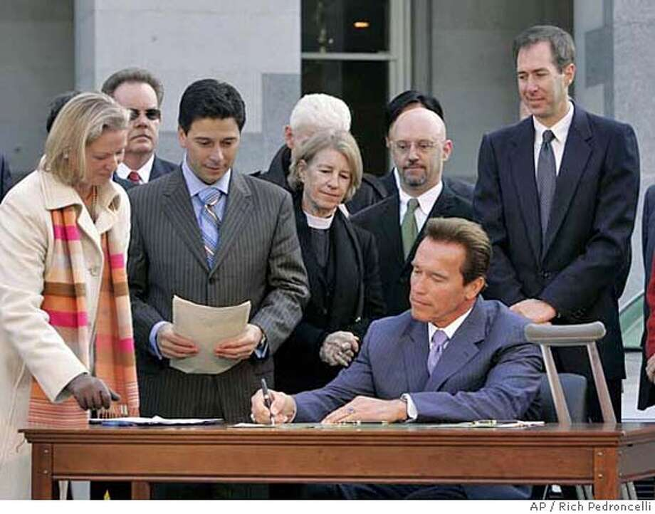 California Gov. Arnold Schwarzenegger, seated, signs an executive order establishing new low carbon fuel standards for transportation fuels sold in the state, as Assembly Speaker Fabian Nunez, second from left, looks on during a ceremony at the state Capitol in Sacramento, Calif., Thursday, Jan. 18, 2007. (AP Photo/Rich Pedroncelli) STAND ALONE Photo: Rich Pedroncelli