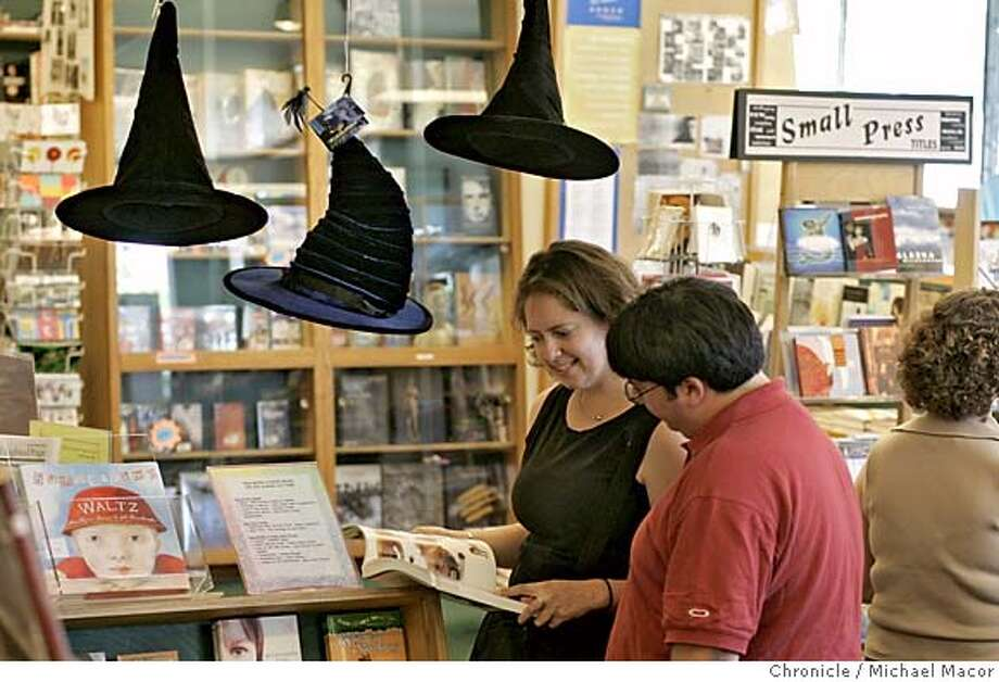 "bookstores_077_mac.jpg Susan Holmes and Rob Glazier, visiting from Michigan, browse through books at ""A Clean Well Lighted Place for Books"", along Van Ness in SF, while Harry Potter hats hang around the store to promote the upcoming release of the next Harry Potter book, ""Harry Potter and the Half-Blood Prince"". Local independent bookstores, which are likely to see their monthly revenues spike by 10 to 30 percent just due to Potter sales, a welcome event during the normally-slow summer season. Many will be holding Potter parties on Friday night. Suggest photo that includes the HP decorations and staff taking phone orders for the book, or selling copies of the older HP books, or talking with customers about the book. 7/13/05 San Francisco, Ca Michael Macor / San Francisco Chronicle Mandatory Credit for Photographer and San Francisco Chronicle/ - Magazine Out Photo: Michael Macor"