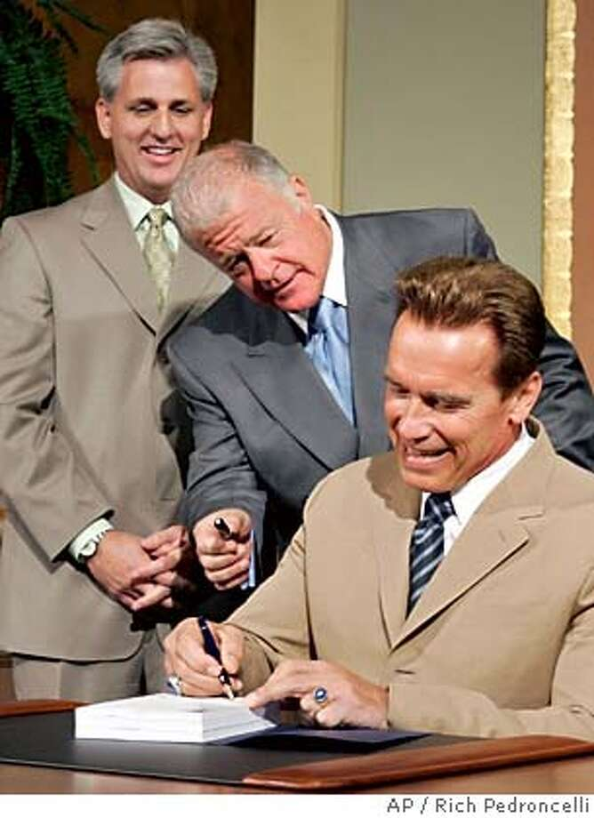 State Sen. President Pro Tem Don Perata, D-Oakland, center, offers his pen to Gov. Arnold Schwarzenegger as he signs the state budget at the Capitol in Sacramento, Calif., Monday, July 11, 2005. Schwarzenegger signed the $117.5 billion 2005-06 spending plan that does not raise taxes and avoids borrowing that has plagued the state in recent years. At left is Assembly Minority Leader Kevin McCarthy, R-Bakersfield. (AP Photo/Rich Pedroncelli) Photo: RICH PEDRONCELLI