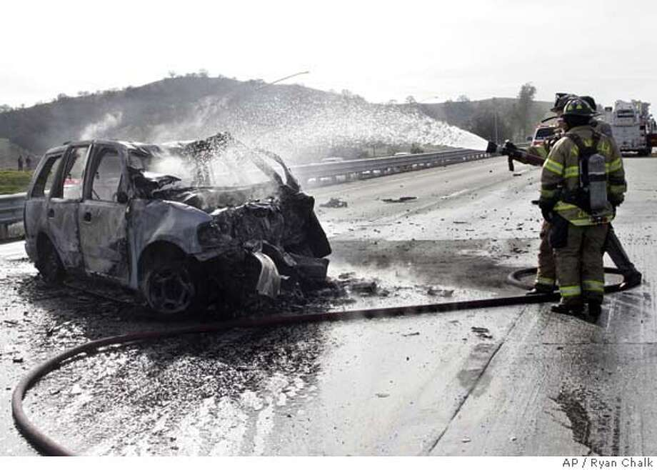Vacaville firefighters spray water on a burned out vehicle involved in a multiple fatality accident on Interstate 80, Saturday, Jan. 20, 2007, in Vacaville, Calif. The fiery collision killed four people and closed down a section of the interstate between San Francisco and Sacramento, less than a day after four others died in a highway crash in Santa Rosa, Calif. Five vehicles were involved in the crash, said California Highway Patrol Officer Marc Johnston. Three of the vehicles involved caught fire, he said. (AP Photo/The Vacaville Reporter, Ryan Chalk) Photo: Ryan Chalk