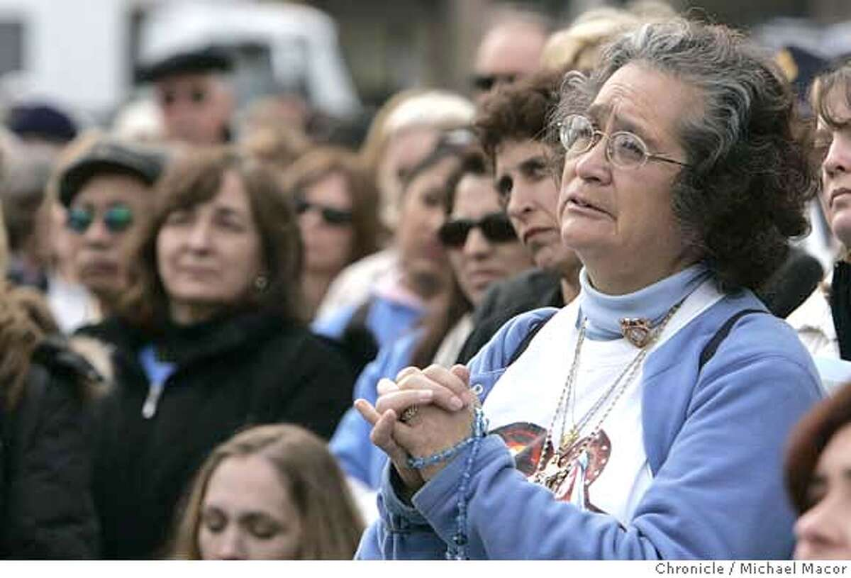 Florine Konkle of San Francisco, clutches rosary beads as listens to a testimony of a woman who had an abortion, at the start of the rally at Justin Herman Plaza. The 3rd annual