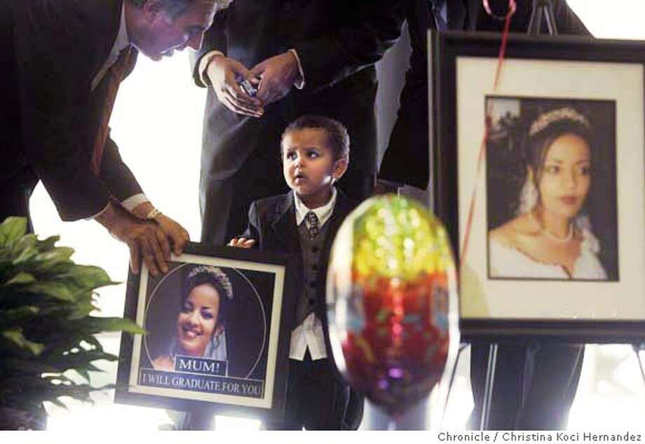 Family of the slain Winta Mehari presents a photo of her to the Cal State East Bay, receiving it is (L)Dr. Mohammad Qayoumi, President of Cal State East Bay,and holding photo is Winta's son, Isaac Abraham Tewolde, age 2. It is a promise that her son will also graduate from a university.  Winta Mehari was killed along with her mother and brother during a Thanksgiving party last fall in North Oakland. Mehari was just completing work on an accounting degree at Cal State East Bay, where she attended classes while also taking care of her young son. On Friday, Cal State will award her degree to Mehari�s family, including her 2-year-old son, in a special campus ceremony. (CHRISTINA KOCI HERNANDEZ/CHRONICLE) CHRONICLE Photos by CHRISTINA KOCI HERNANDEZ Photo: CHRISTINA KOCI HERNANEZ/CHRONICL