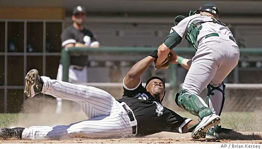 Oakland Athletics catcher Adam Melhuse, right, tags out Chicago White Sox's Frank Thomas after Thomas tried to score from second base on a single hit by Aaron Rowand during the first inning, Sunday, July 10, 2005, in Chicago. (AP Photo/Brian Kersey) Photo: BRIAN KERSEY