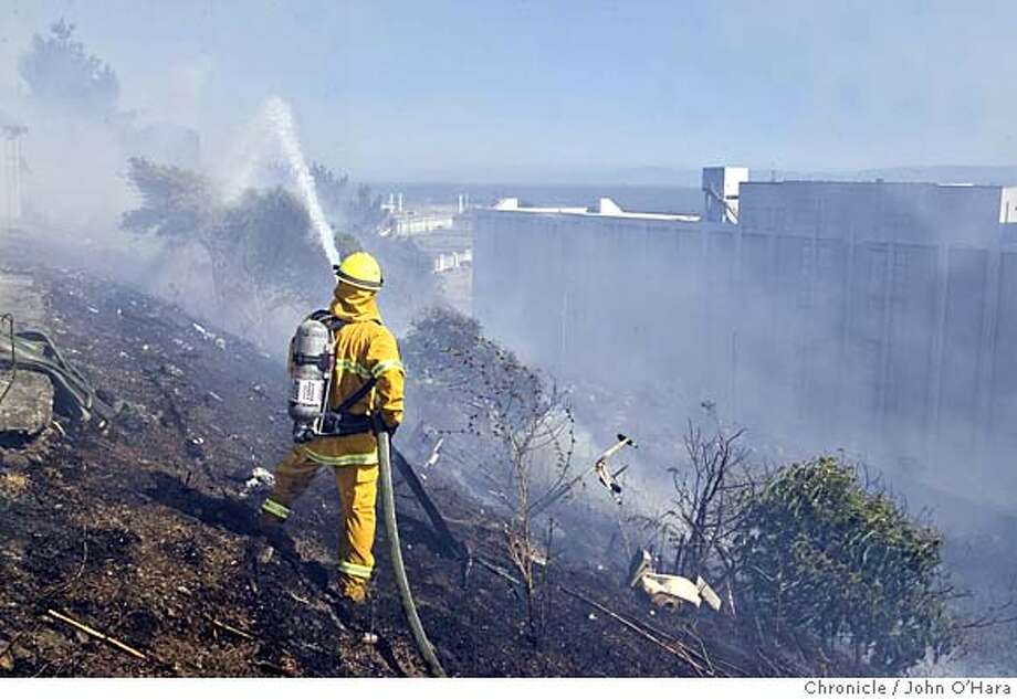BAYVIEW/ HUNTERS POINT  Mike Peterson of Engine 44, works on hots spots as the fire reached the back fences of some of the town houses.  A fifty acre grass fire went around the hillside in the bay view this afternoon.  Photo/ John O'hara