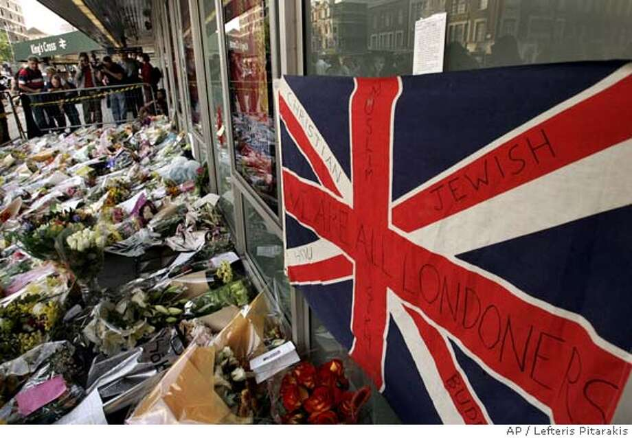A message is written on a British flag among the flower tributes left outside Kings Cross Station in London, Saturday July 9, 2005, as people paid their respects following Thursday's bombings. Police revised the timing of the deadly blasts that tore through the London Underground, saying on Saturday the explosions were detonated just seconds apart and were so powerful that none of the 49 dead have been identified and bodies remain trapped deep inside a subway tunnel. Hundreds have been reported missing. (AP Photo/Lefteris Pitarakis) Photo: LEFTERIS PITARAKIS