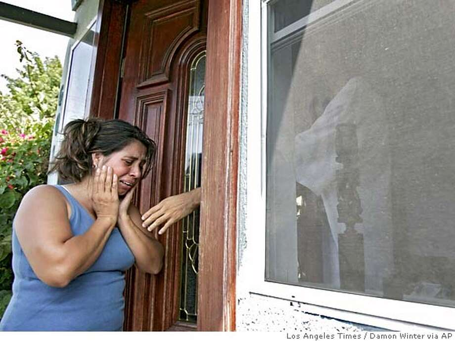 ** CORRECTS TO PENA STED LEMOS ** Lorena Lopez, wife of Jose Raul Pena, cries outside her home in South Los Angles Monday, July 11, 2005, as a family member reaches through the front doorway to comfort her. Pena and the couple's young daughter were shot and killed Sunday in a gun battle with police near his home. Pena apparently used his daughter as a shield during the standoff. (AP Photo/Los Angeles Times, Damon Winter) ** MANDATORY CREDIT: Damon Winter/Los Angeles Times, , NO FOREIGN, NO MAGS, TV OUT, LOS ANGELES DAILY NEWS OUT, ORANGE COUNTY REGISTER OUT, VENTURA COUNTY STAR OUT, INLAND VALLEY DAILY BULLETIN OUT, SAN BERNARDINO SUN OUT ** ** CORRECTS TO PENA STED LEMOS ** MANDATORY CREDIT: DAMON WINTER/LOS ANGELES TIMES, , NO FOREIGN, NO MAGS, TV OUT, LOS ANGELES DAILY NEWS OUT, ORANGE COUNTY REGISTER OUT, VENTURA COUNTY STAR OUT, INLAND VALLEY DAILY BULLETIN OUT, SAN BERNARDINO S Photo: DAMON WINTER