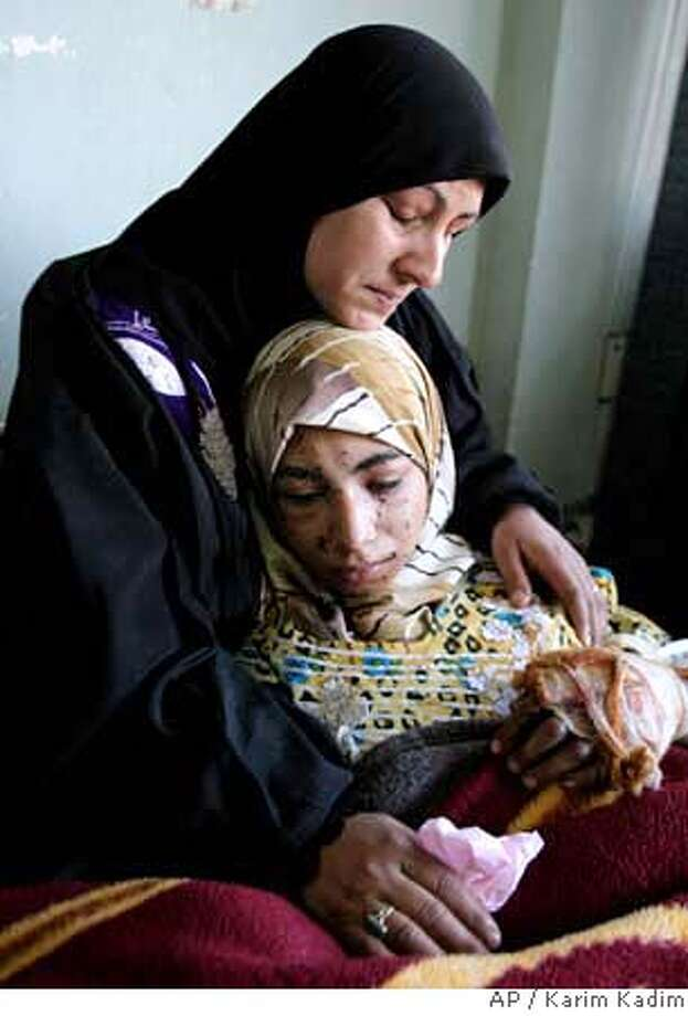 A mother, no first name available, comforts her 18-year-old daughter Fatimah Krim at a hospital in Baghdad, Iraq, Wednesday Jan. 17, 2007. Fatimah was injured Tuesday when twin car bombs exploded at a leading Baghdad university Tuesday as students left classes in the deadliest attack in Iraq in nearly two months killing at least 65 students. (AP Photo/Karim Kadim) Photo: KARIM KADIM
