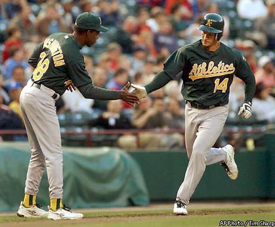 Oakland Athletics' Mark Ellis (14) is congratulated by third base coach Ron Washington (38) after hitting a solo home run off Texas Rangers pitcher Ismael Valdez during the third inning, Wednesday night, April 9, 2003, in Arlington, Texas. (AP Photo / Tim Sharp) Photo: TIM SHARP