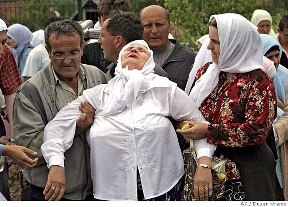 A woman is helped by her relatives during a funeral of 610 Bosnian Muslims killed by advancing Bosnian Serb forces in Potocari, outside Srebrenica on the 10th anniversary of the Srebrenica massacre, Monday, July 11, 2005. Toward the end of Bosnia's 1992-95 war, as many as 8,000 Bosnian Muslim men and boys were killed when Bosnian Serb troops overran the eastern Bosnian enclave of Srebrenica July 11, 1995. It was Europe's worst mass killing since World War II. (AP Photo/Dusan Vranic) Photo: DUSAN VRANIC