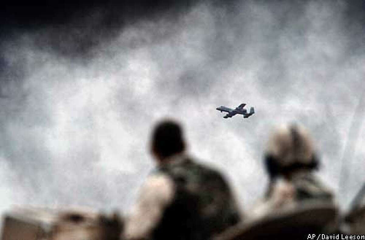 One of two A-10 Warthog planes circles past smoke from burning Republican Guard barracks in northern Baghdad, Tuesday, April 8, 2003. One of the planes was later hit by an Iraqi surface-to-air-missile forcing the pilot to eject. The pilot was safely recovered. (AP Photo/Dallas Morning News, David Leeson)