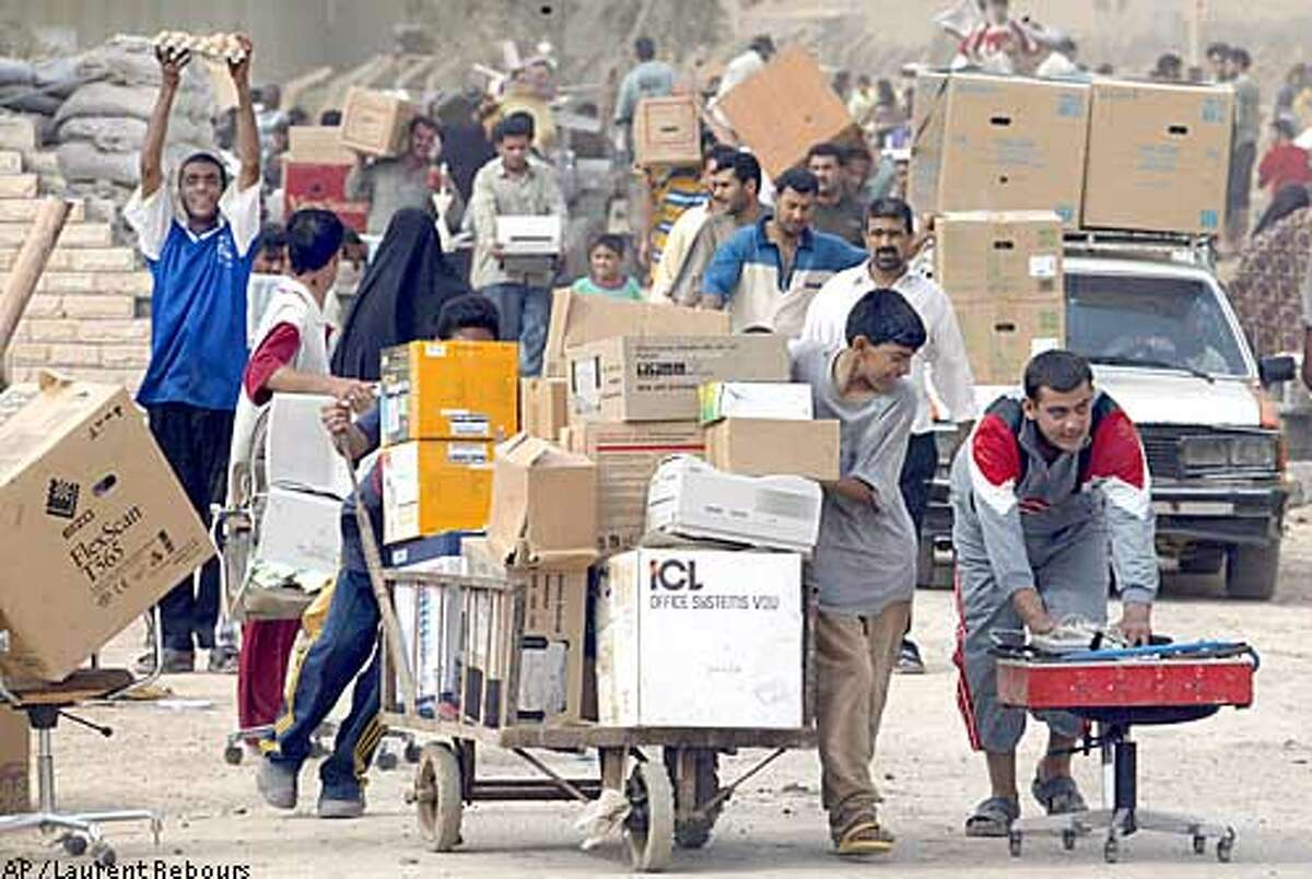 Iraqi civilians push carts loaded with goods after looting a government warehouse on a main road leading into Baghdad in a southeastern suburb of the Iraqi capital, Wednesday, April 9, 2003. (AP Photo/Laurent Rebours)