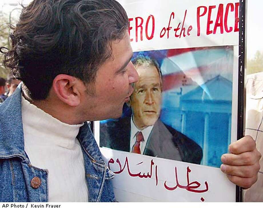 A Kurd kisses a picture of United States President George W. Bush during celebrations in the streets of Sulaymaniyah, northern Iraq Wednesday April 9, 2003. Celebrations broke out in at least two cities in the Kurdish autonomous region, as people took to the streets to celebrate what they believe is the end of President Saddam Hussein's regime. (AP Photo/Kevin Frayer) Photo: KEVIN FRAYER
