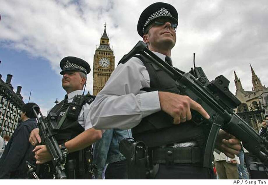 Two armed police officers patrol outside the Houses of Parliament in London Friday, July 8, 2005 as security is tightened after yesterday's series of explosions in the underground trains and a double-decker bus. More than 50 people died in four terrorist bombings in London, but emergency workers have not been able to reach some of the dead deep underground in a subway car because of fears the tunnel could collapse, the city's police chief said Friday. (AP Photo/Sang Tan) Photo: SANG TAN