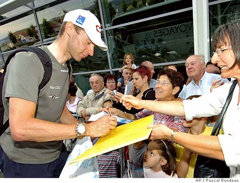 Overall leader Jens Voigt of Germany signs autograhs as he arrives at the Grenoble airport, after the ninth stage of the 92nd Tour de France cycling race between Gerardmer and Mulhouse, eastern France, Sunday, Juy 10, 2005. The tour resumes Tuesday. (AP Photo/Pascal Rondeau, Pool) Photo: PASCAL RONDEAU