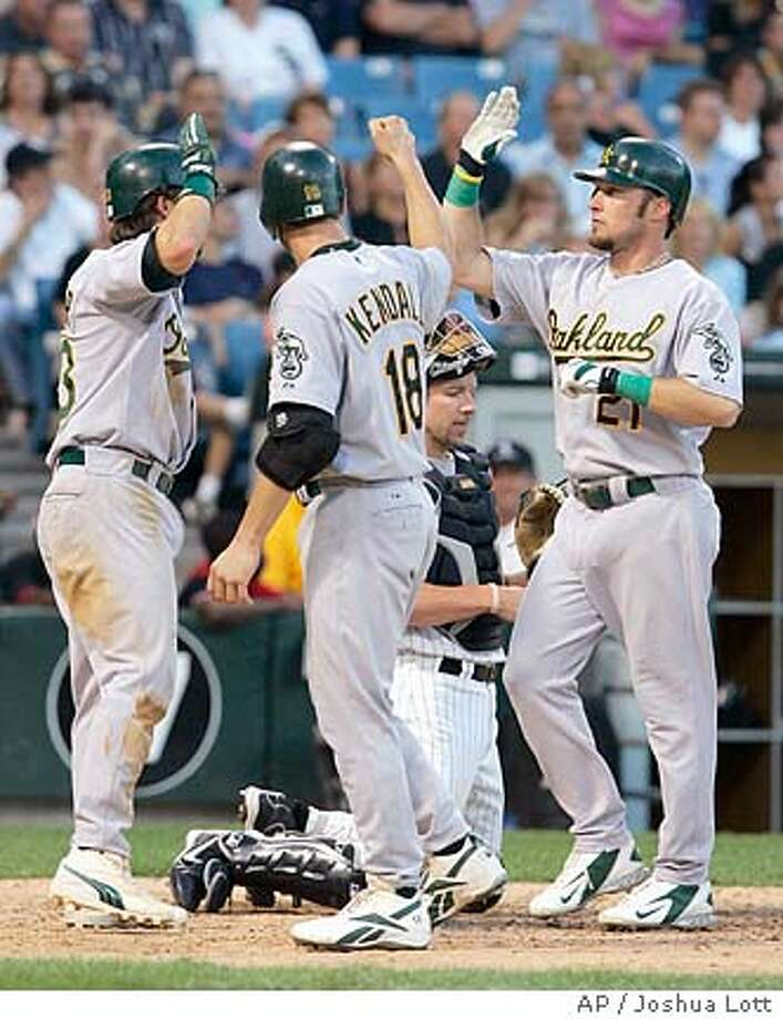 **NY**Oakland Athletics Mark Kotsay (21) is greeted at home plate by Jason Kendall (18) and Nick Swisher after hitting a three-run home run in the seventh inning against the Chicago White Sox, Saturday, July 9, 2005, In Chicago. (AP Photo/Joshua Lott.) Photo: AP/JOSHUA LOTT