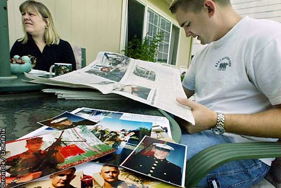 Kevin Outman, 26 years old, brother of Army PFC Brian Outman, watches CNN and reads news articles to catch the latest news on the war. He hasn't heard much about/from his younger brother since the the start of the war, until a mention of Brian in yesterday's Chronicle. In front are some of Kevin's pictures of Brian when he was in training. (PHOTOGRAPHED BY LIZ HAFALIA/THE SAN FRANCISCO CHRONICLE) Photo: LIZ HAFALIA