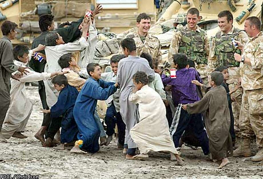British Soldiers from 16 Air Assault Brigade throw chocolate bars from their ration packs to Iraqi children, in the village of Qaryat Nasr north of of the city of Basra, in southern Iraq, April 7, 2003. British and U.S. troops walked unopposed almost to the center of Basra for the first time on Monday, with Britain's Defense Secretary Geoff Hoon saying that British forces had moved to the heart of the city and were there to stay. REUTERS/POOL/Chris Ison Photo: POOL