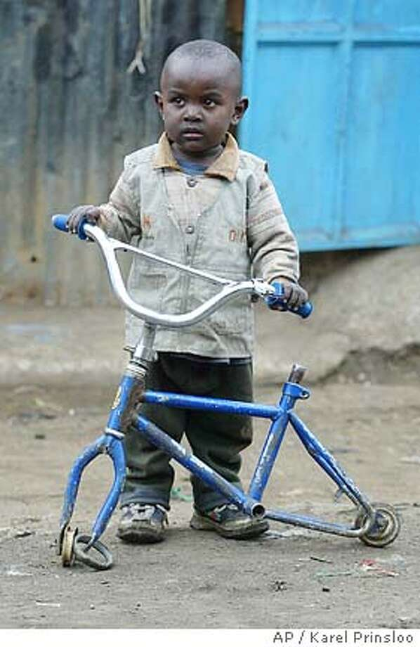 A young boy holds a broken bicycle, Friday, July 1, 2005 in the Kibera slum in Nairobi. When the leaders of the world's wealthiest nations meet during the G8 summit to discuss helping the poorest people on the planet, they will try to ensure any new pledges will not be good money following bad. British Prime Minister Tony Blair and his Commission for Africa say that times have changed, and the world now has a chance to reverse the continent's economic and social decline.(AP Photo/Karel Prinsloo) JULY 1, 2005 PHOTO Photo: KAREL PRINSLOO