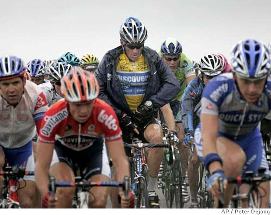 Overall leader, six-time Tour de France winner and leader of the Discovery Channel cycling team, Lance Armstrong of Austin, Texas, rear center, zips up his rain jacket as he pedals in the pack during the sixth stage of the Tour de France cycling race between Troyes and Nancy, eastern France, Thursday, July 7, 2005. (AP Photo/Peter Dejong) Photo: PETER DEJONG