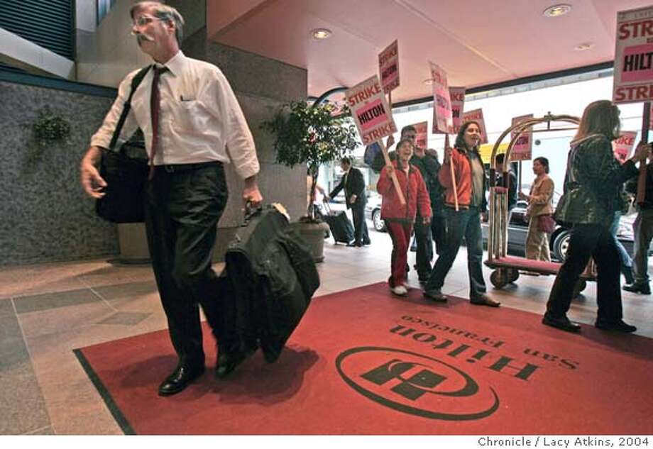 Customers still chech in at the Hilton Hotel as protesters from Local Union 2 hotel workers march the the doors claiming ongoing unfair labor practices, in San Francisco, Sept.29, 2004. The Person with the suitcase, checking in, declined to give his name.  LACY ATKINS/ The Chronicle MANDATORY CREDIT FOR PHOTOG AND SF CHRONICLE/ -MAGS OUT Photo: LACY ATKINS