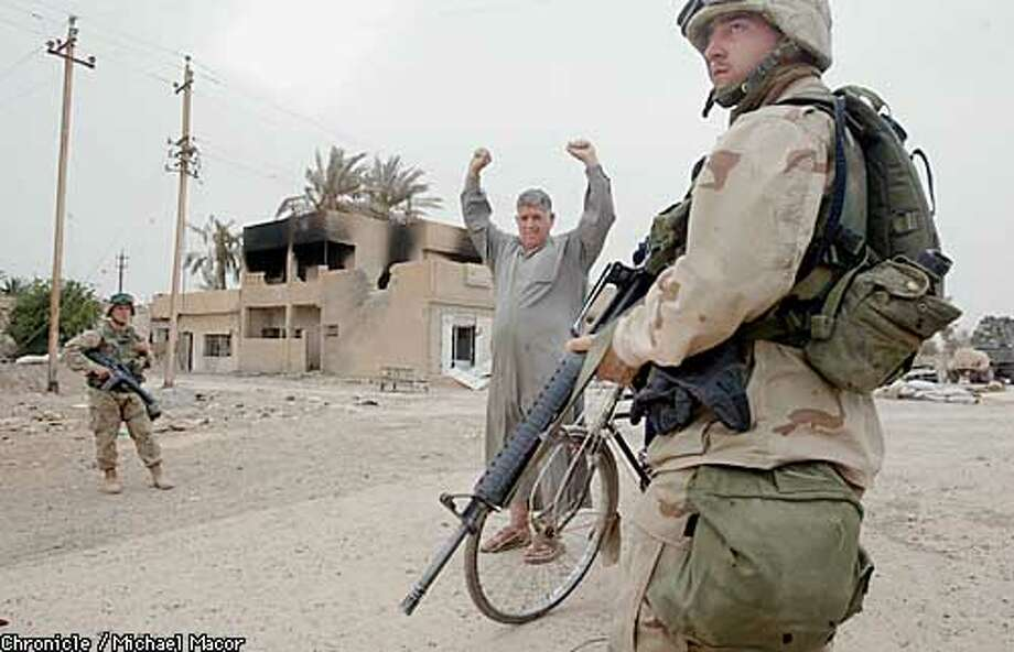 Iraqi's who found themselves north of the Diyali River are escorted back across the bridge to their home. Hands raised to signal to Marines they are only resdients. by Michael Macor/The Chronicle Photo: MICHAEL MACOR