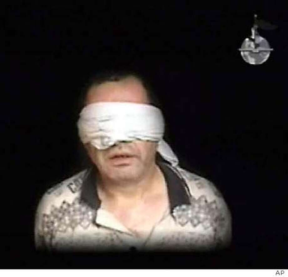 """Egypt's envoy to Iraq Ihab el-Sherif is shown speaking at an unknown location in Iraq while blindfolded in this frame grab from a video posted on an internet site on July 7, 2005. The Al Qaeda group in Iraq said on Thursday it killed Egypt's top envoy to Iraq for representing a """"tyrannical"""" government allied to the """"Jews and Crusaders"""". The group, led by Abu Musab al-Zarqawi, posted a video showing the hostage speaking but not the actual killing. A senior Egyptian official said that Cairo has no independent information about the fate of the envoy and is relying on media reports and Internet postings. REUTERS/Handout Photo: HO"""