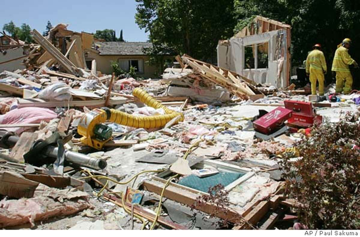 Rescue workers look over the rubble of the home of David Hu in Los Altos, Calif., Thursday, July 7, 2005 after a , authorities said. Two children, ages 4 and 6, were treated for minor injures after the blast at the two-story home that destoyed most of the house. (AP Photo/Paul Sakuma)