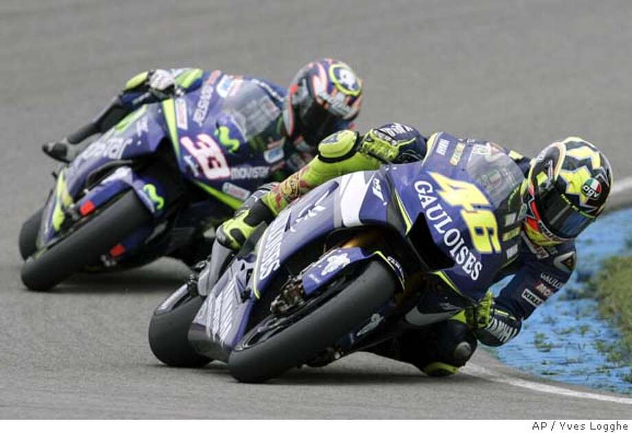 Valentino Rossi of Italy, right, steers his Yamaha, into the curb chased by Marco Melandri of Italy with his Honda during the MotoGP of the Assen GP in Assen, northern Netherlands, Saturday June 25, 2005. Rossi won the race, second was Melandri, third placed Colin Edwards of the USA with his Yamaha. (AP Photo/Yves Logghe) Photo: YVES LOGGHE