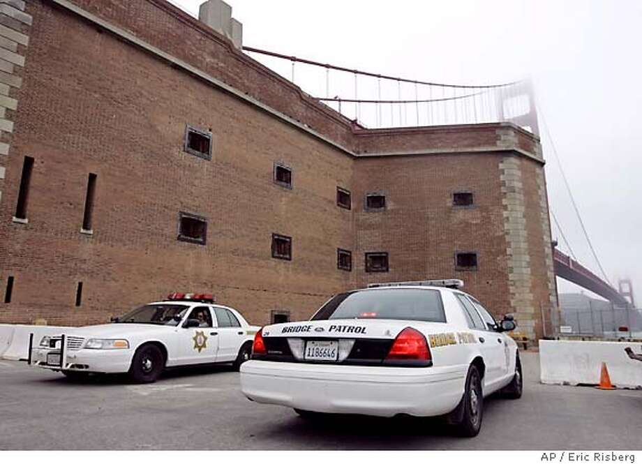 A pair of Golden Gate Bridge Patrol cars maintain a watch at Fort Point below the Golden Gate Bridge in San Francisco, Thursday July 7, 2005. Officials from Los Angeles to San Francisco reacted to a series of bombings in London Thursday by increasing security at train stations and airports and the Bush administration raised the terror alert a notch to code orange.(AP Photo/Eric Risberg) Photo: ERIC RISBERG
