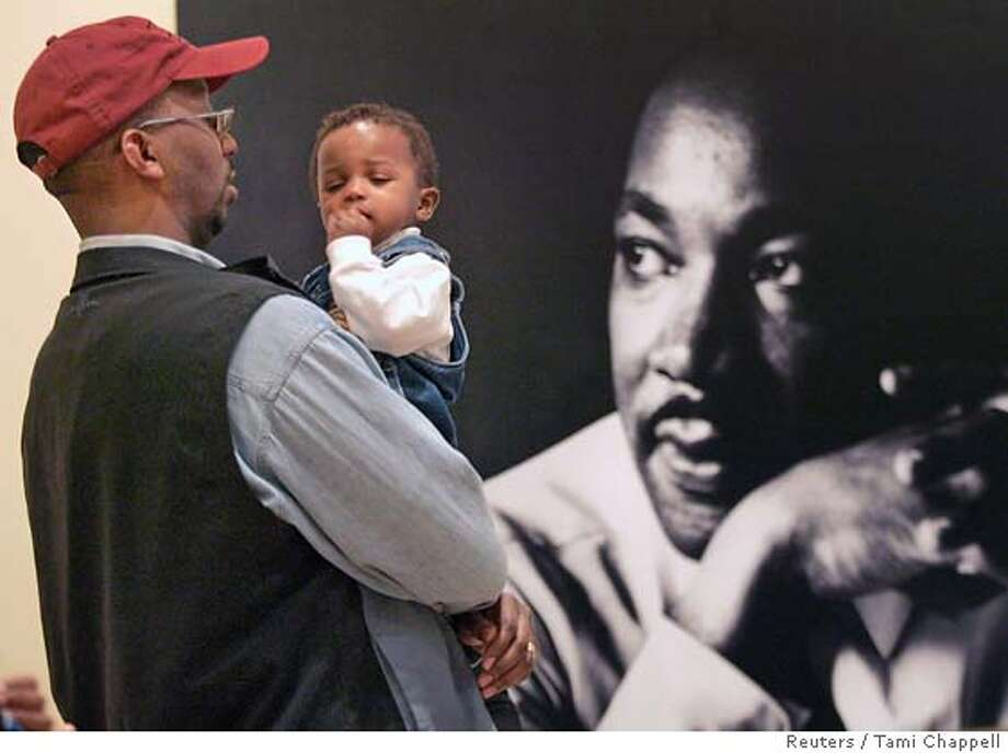 Brendon Barclay holds son Bryce as he visits the Morehouse College Martin Luther King, Jr. collection at the Atlanta History Center which opened on the King Holiday in Atlanta, Georgia, January 15, 2007. The collection includes handwritten personal notes and unpublished sermons by the civil rights leader and documents his civil rights campaign. REUTERS/Tami Chappell (UNITED STATES) 0 Photo: TAMI CHAPPELL