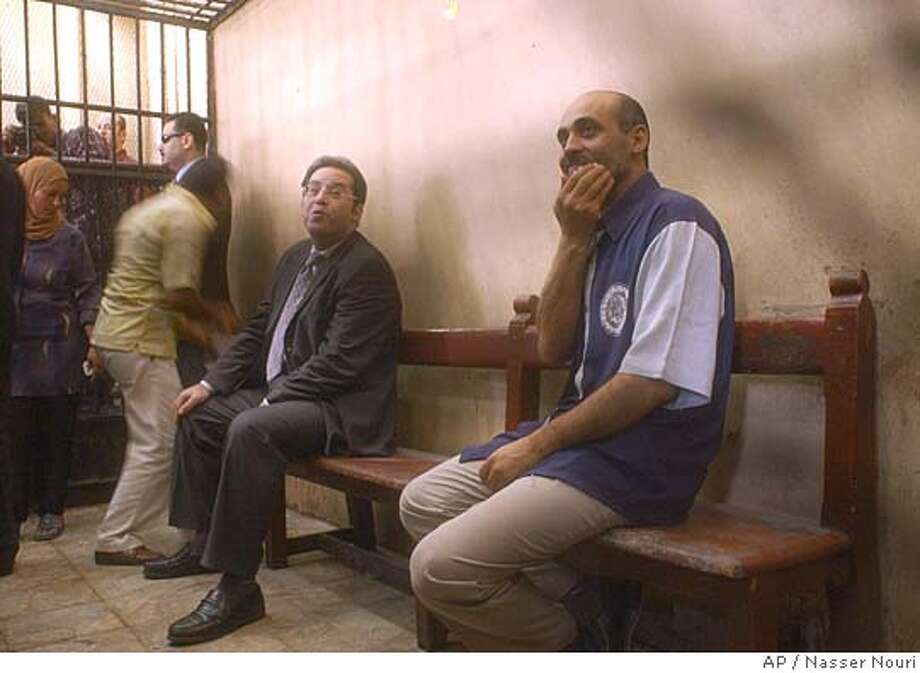 Top opposition leader and presidential candidate Ayman Nour, left, sitting in a cage in the courtroom beside defendant Ayman Hassan who said Wednesday July 6, 2005 that Nour has nothing to do with the alleged forgery of election registrations, saying security agents forced him to make the claims. The trial was adjourned till Sept. 25, 2005. (AP Photo/Nasser Nouri) Photo: NASSER NOURI