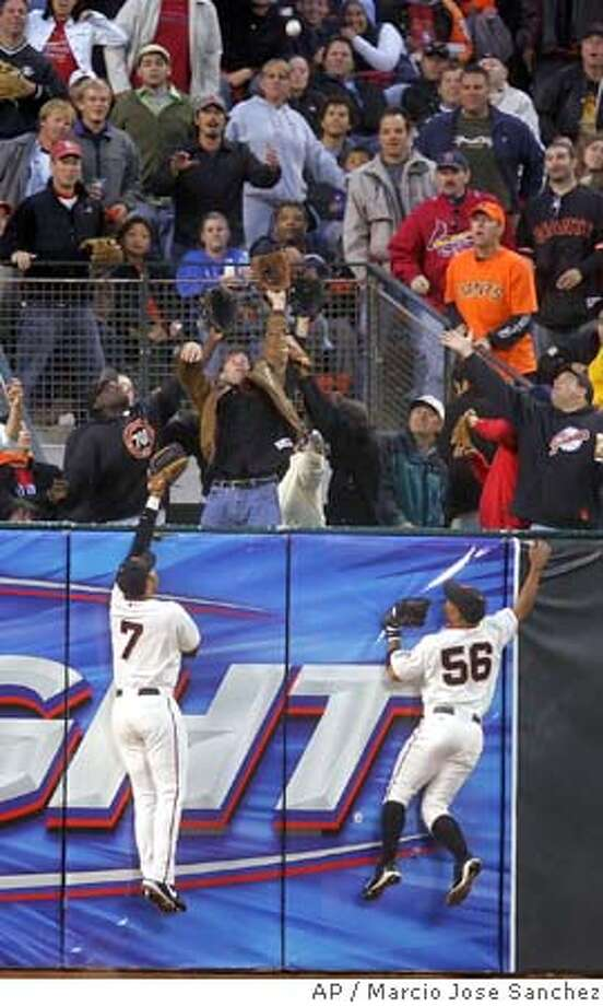 San Francisco Giants left fielder Pedro Feliz (7) and center fielder Jason Ellison (56) make a leaping attempt at the wall on a line drive by the St. Louis Cardinals' Reggie Sanders in the fourth inning on Friday, July 8, 2005 in San Francisco, Calif. Sanders got a solo home run on the play. (AP Photo/Marcio Jose Sanchez) Photo: MARCIO JOSE SANCHEZ