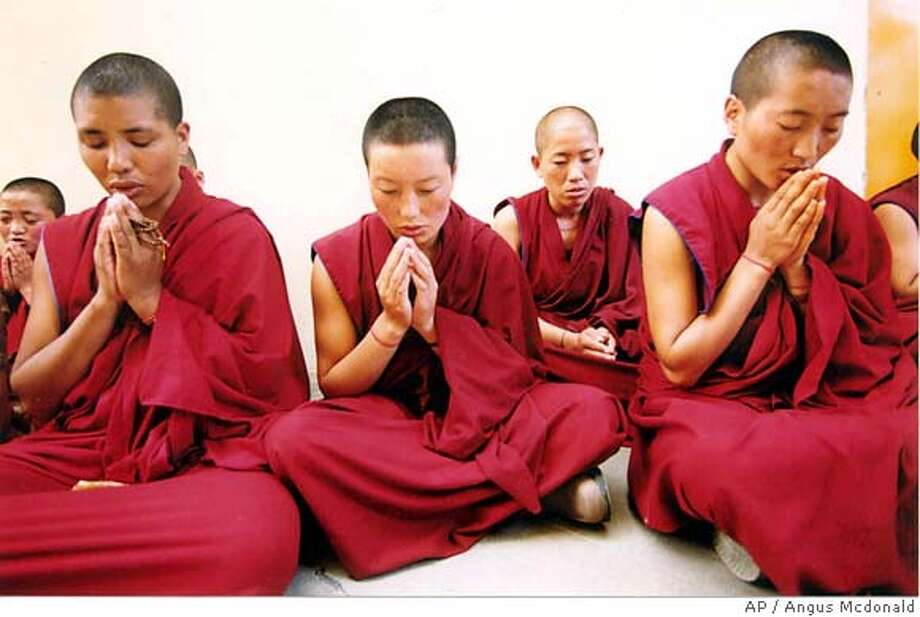 Tibetan nuns in Dharamsala pray Sept. 12, 2001, for the victims of terrorist attacks in the United States one day earlier. Associated Press file photo by Angus Mcdonald