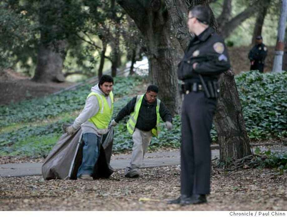 A crew clears away belongings and debris to a dump truck as a police officer stands guard. UC police raided the base camp for tree-sitting protesters in front of Memorial Stadium in Berkeley, Calif. on Friday, Jan. 12, 2007. Police made no arrests when they made the pre-dawn raid but confiscated personal belongings of the campers. The tree sitters were not not disturbed and remain in the camped in the limbs.  PAUL CHINN/The Chronicle Photo: PAUL CHINN