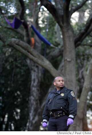 A police officer stands in the grove of trees during the raid. UC police raided the base camp for tree-sitting protesters in front of Memorial Stadium in Berkeley, Calif. on Friday, Jan. 12, 2007. Police made no arrests when they made the pre-dawn raid but confiscated personal belongings of the campers. The tree sitters were not not disturbed and remain in the camped in the limbs.  PAUL CHINN/The Chronicle Photo: PAUL CHINN