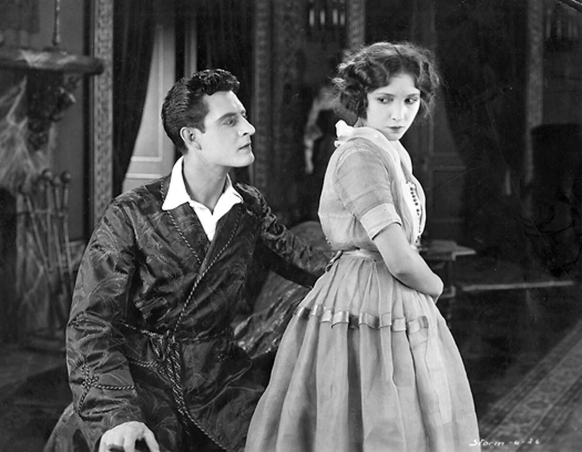 The fascinatingly romantic St. Elmo Murray, in the person of John Gilbert, is here shown giving Edna Earl to understand that he takes more than a passing interest in her. Edna, playing by pretty Bessie Love, cannot but listen although she fears the young gentleman. The scene is from the William Fox production of the famous novel
