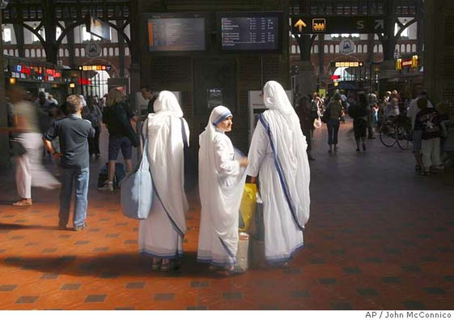 Sisters of Charity look for their train platform at Copenhagen Central Rail Station Thursday July 7, 2005. Four blasts rocked the London subway and tore open a packed double-decker bus during the morning rush hour Thursday. Police have asked passengers and security personnel at Copenhagen transportation hubs to be more vigilant in the wake of the attacks and a group claiming responsibility for the attacks has threatened Italy and Denmark. (AP Photo/John McConnico) Photo: JOHN MCCONNICO