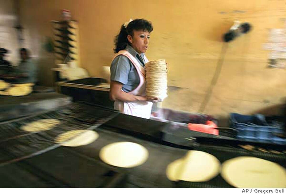 Tortilla maker Leticia Balino gathers a pile of tortillas in her shop in Mexico City, Mexico, Wednesday, Jan. 10, 2007. Tortillas, one of Mexico's most closely regulated commodities, rose in price this month, from seven to ten pesos for one kilo. (AP Photo/Gregory Bull) TO GO WITH STORY ON TORTILLA PRICES BY PETER ORSI EFE OUT