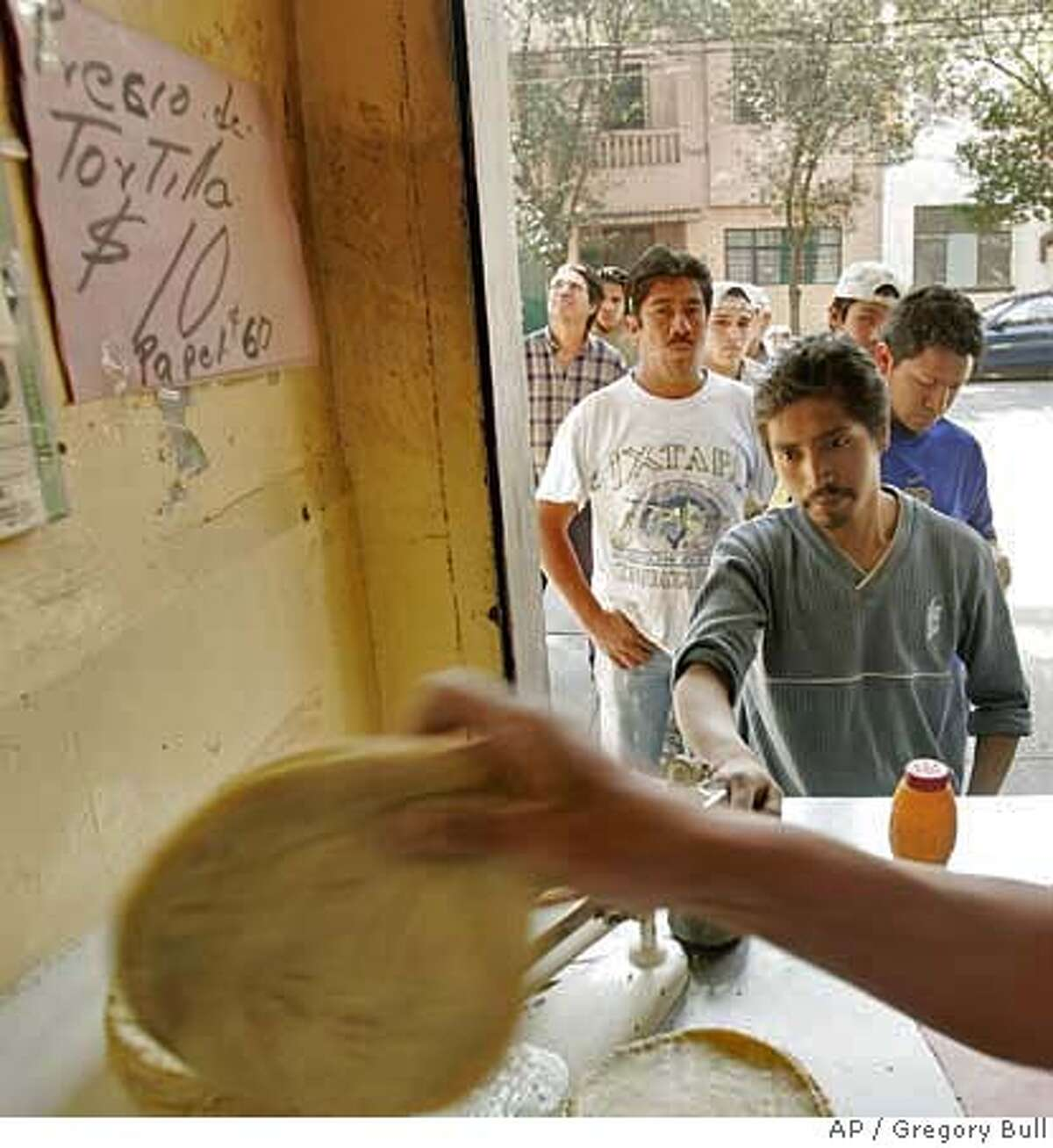 Men wait for tortillas at a tortilla shop in Mexico City, Mexico, Wednesday, Jan. 10, 2007. Tortillas, one of Mexico's most closely regulated commodities, rose in price this month, from seven to ten pesos for one kilo. (AP Photo/Gregory Bull) TO GO WITH STORY ON TORTILLA PRICES BY PETER ORSI EFE OUT