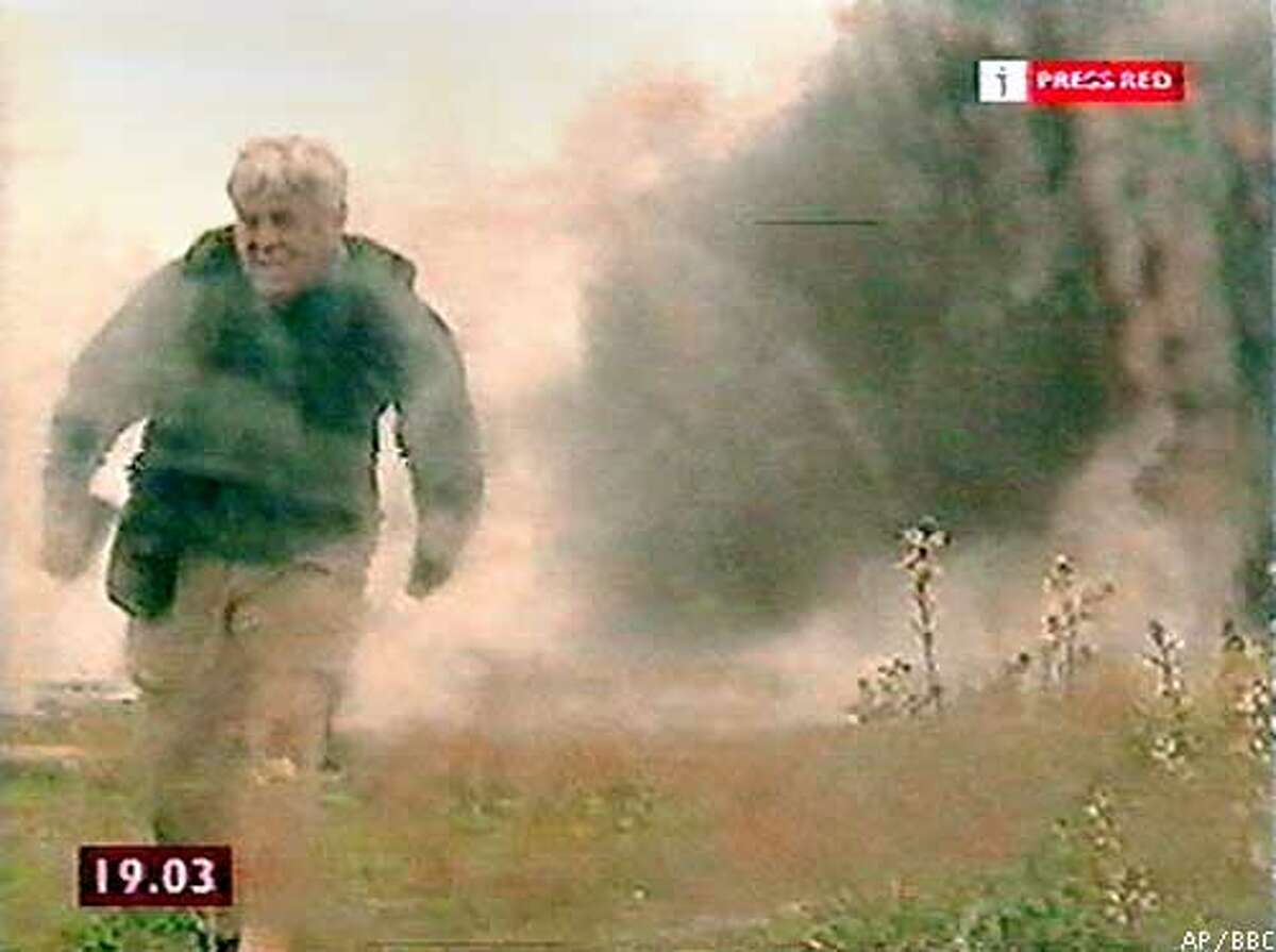 In this video image from BBC News 24, BBC journalist John Simpson runs from the scene after U.S. warplanes reportedly struck a convoy of allied Kurdish fighters and U.S. Special Forces near Mosul, northern Iraq, Sunday, April 6, 2003. At least 18 people were killed and more than 45 wounded, including senior Kurdish commanders, Kurdish officials said. Simpson was among those injured in the incident. (AP Photo/BBC News 24) ** ONE TIME USE; TV OUT; ONLINE OUT; NO ARCHIVE; ; MAGS OUT **