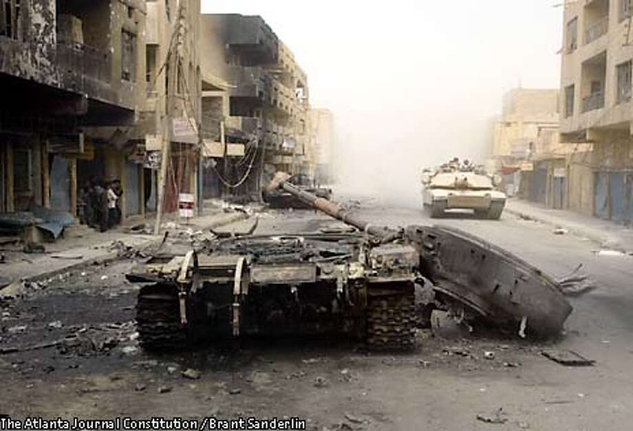 A destroyed Iraqi tank sits in the street of a Baghdad suburb Friday, April 4, 2003. The tank was destroyed the day before by members of 1-64 Task Force 3rd Infantry Division. (AP Photo/Atlanta Journal Constitution, Brant Sanderlin) Photo: BRANT SANDERLIN