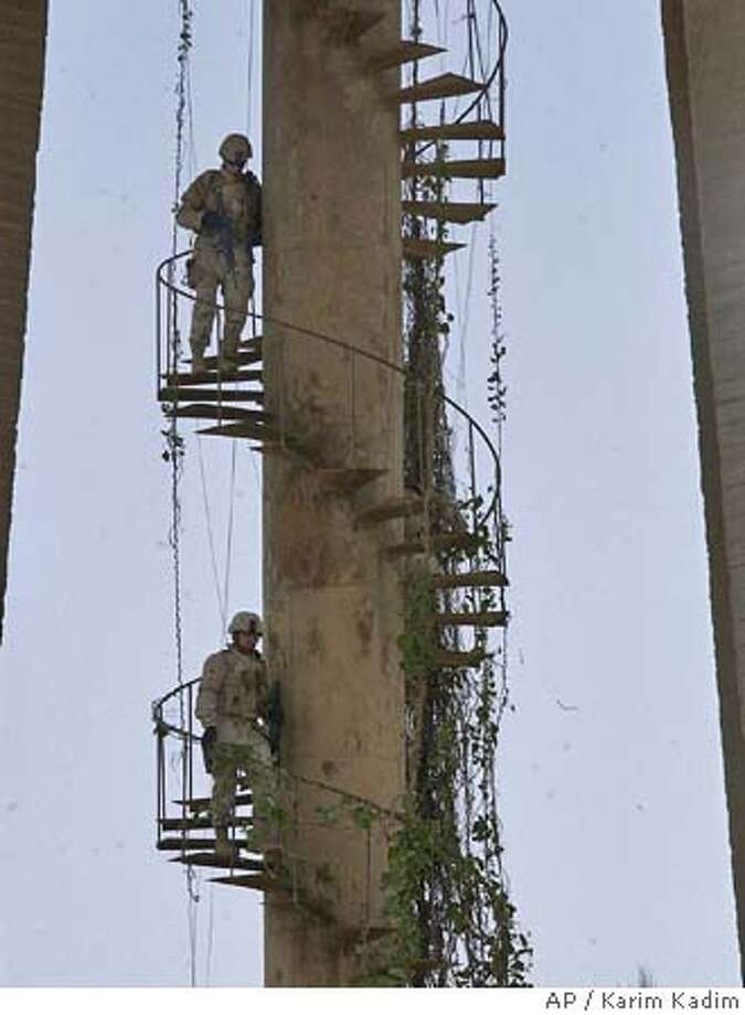 U.S. soldiers climb down a spiral staircase attached to a water tower as they search the area after an explosive device was detonated near a tunnel in central Baghdad, Iraq Wednesday, July 6, 2005. There were no reports of injuries in the blast and no arrests made in the area. (AP Photo/Karim Kadim) Photo: KARIM KADIM