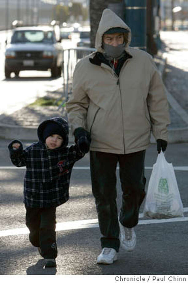 Mario Lopez (right) crosses the street with his grandson Pablo Spinola near the Ferry Building in San Francisco, Calif. on Thursday, Jan. 11, 2007. The family is vacationing from Mexico and aren't used to cold weather. Arctic air is moving into Northern California dropping temperatures for the next few days.  PAUL CHINN/The Chronicle  **Mario Lopez, Pablo Spinola Photo: PAUL CHINN