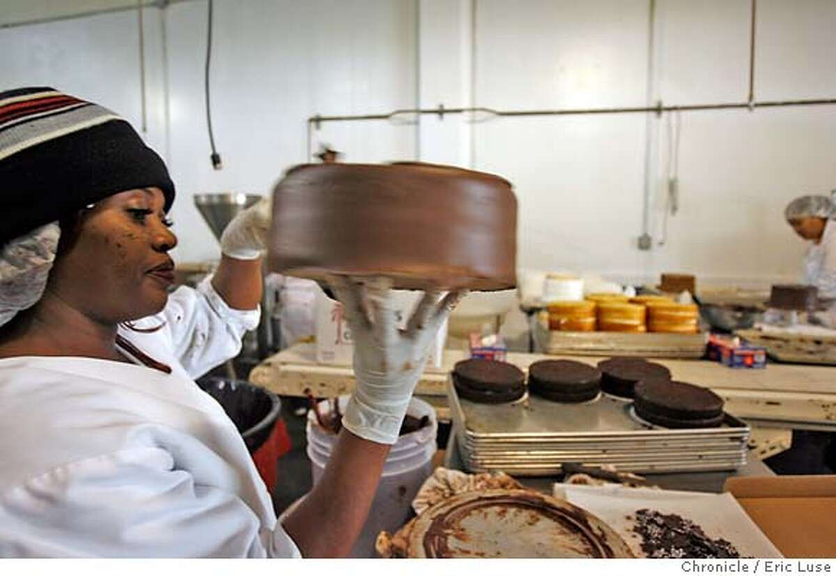Cake decorator Tammy Griffin puts finishing touches on a chocolate cake at the Rubicon Bakery in Richmond, which is supported by young philanthropists. Chronicle photo by Eric Luse