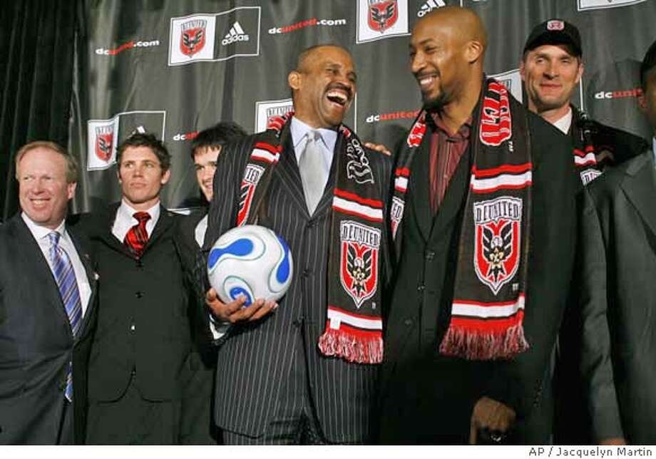 Victor B. MacFarlane, front left, the new majority owner of D.C. United soccer team, jokes with one of the co-owners Brian K. Davis, next to Christian Laettner, far right, after a news conference announcing D.C. United's new ownership in Washington Monday Jan. 8, 2007. At rear left is D.C. United President Kevin Payne. (AP Photo/Jacquelyn Martin) Photo: Jacquelyn Martin