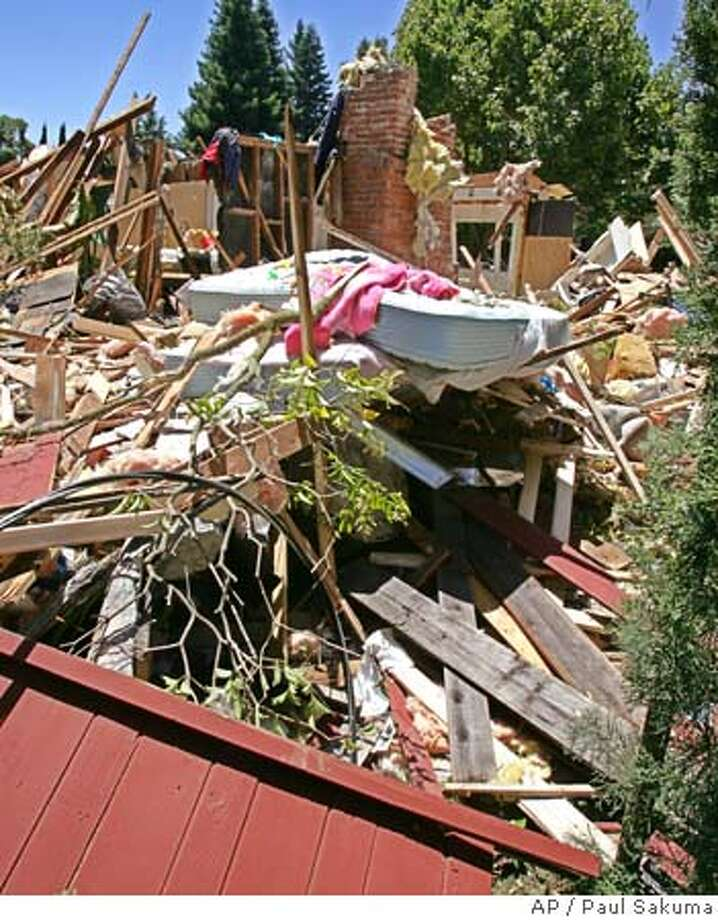 A child's bed is shown in the middle of the rubble of the home of David Hu in Los Altos, Calif., Thursday, July 7, 2005 after a , authorities said. Two children, ages 4 and 6, were treated for minor injures after the blast at the two-story home that destoyed most of the house. (AP Photo/Paul Sakuma) Photo: PAUL SAKUMA