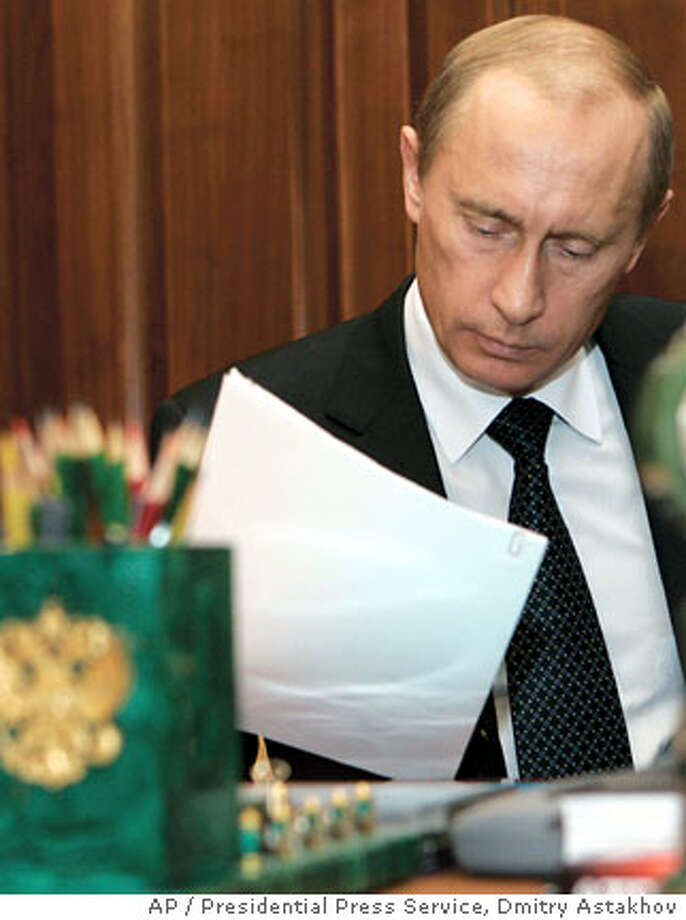 Russian President Vladimir Putin looks at a document at his study in the Moscow Kremlin, Monday, Dec. 4, 2006. Italian Foreign Minister Massimo D'Alema, who meets in Moscow Tuesday with Russian President Vladimir Putin, has pledged to press Russian authorities to help in the investigation of the poisoning death of a former KGB agent in London. (AP Photo/ , Dmitry Astakhov) Photo: ITAR-TASS